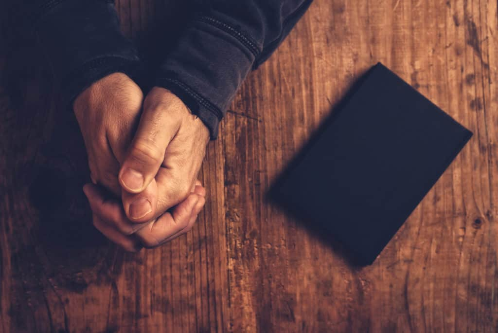 overhead view of a man's praying hands and a black bible beside him on a wooden desk as he contemplates the gift of prophecy