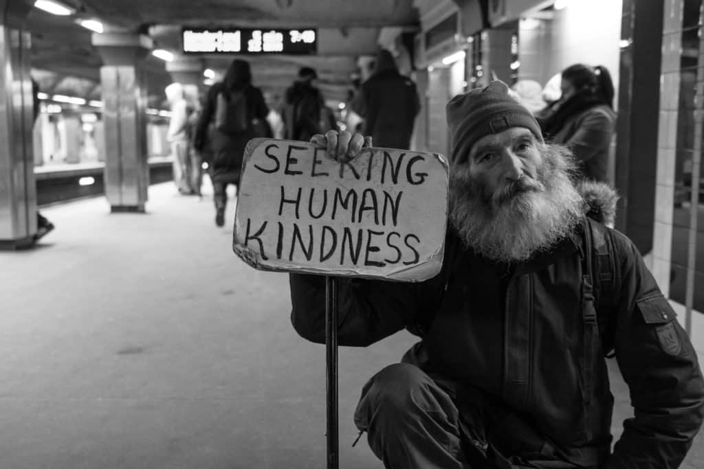 A homeless man holding a sign that says 'seeking human kindness'