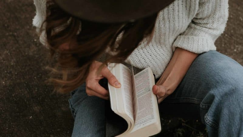 A woman sitting outside reading her Bible as we learn the importance of spending time in the Word of God