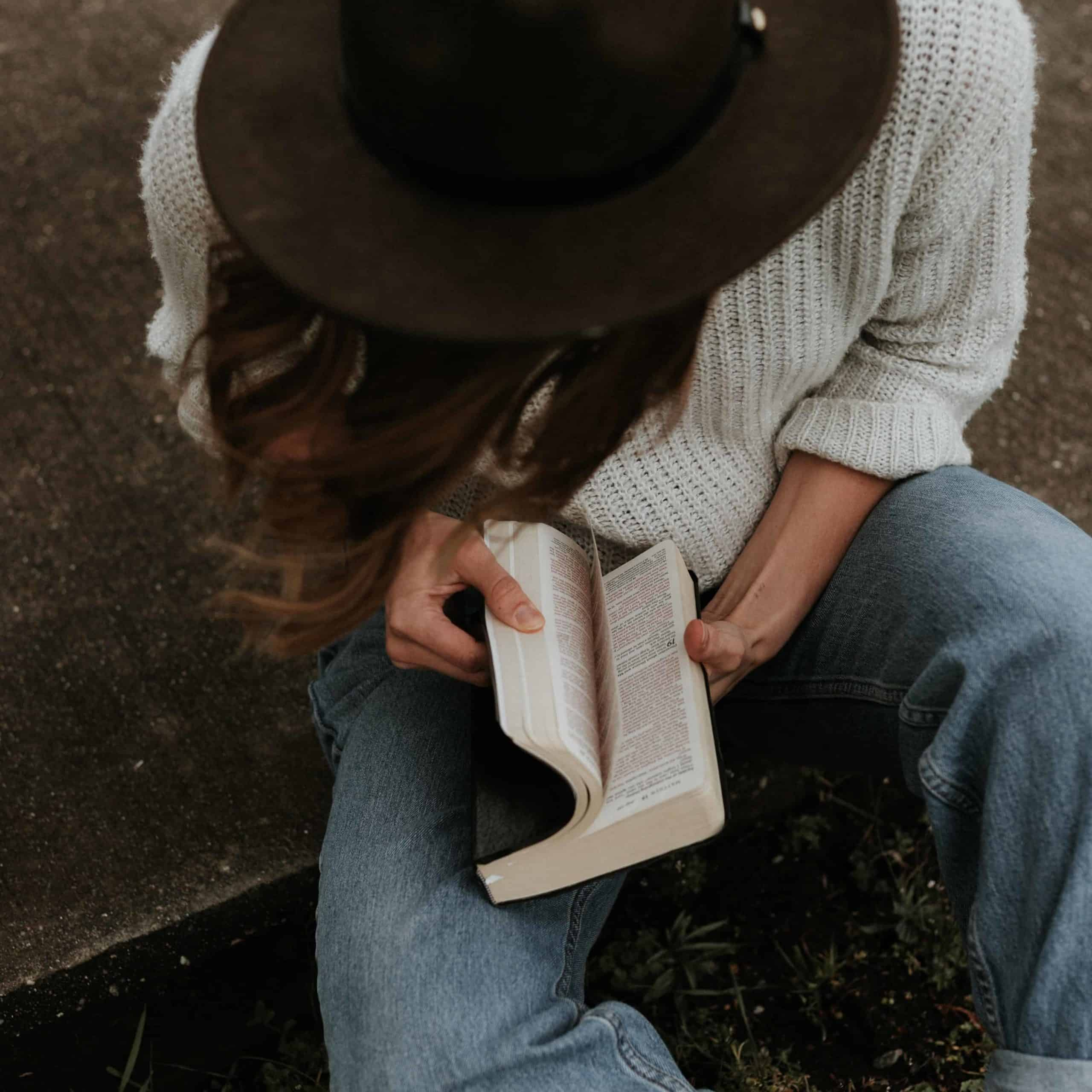 A woman sitting outside reading her Bible.