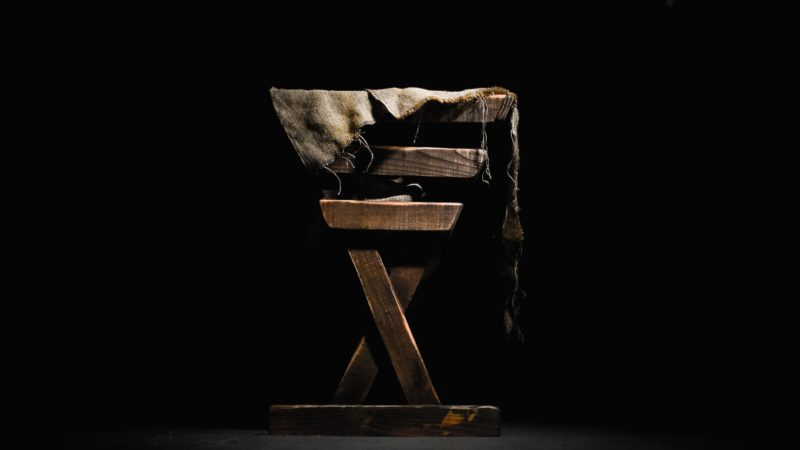 A manger against a black background as we study the birth of Jesus in a humble manner in a stable in Bethlehem