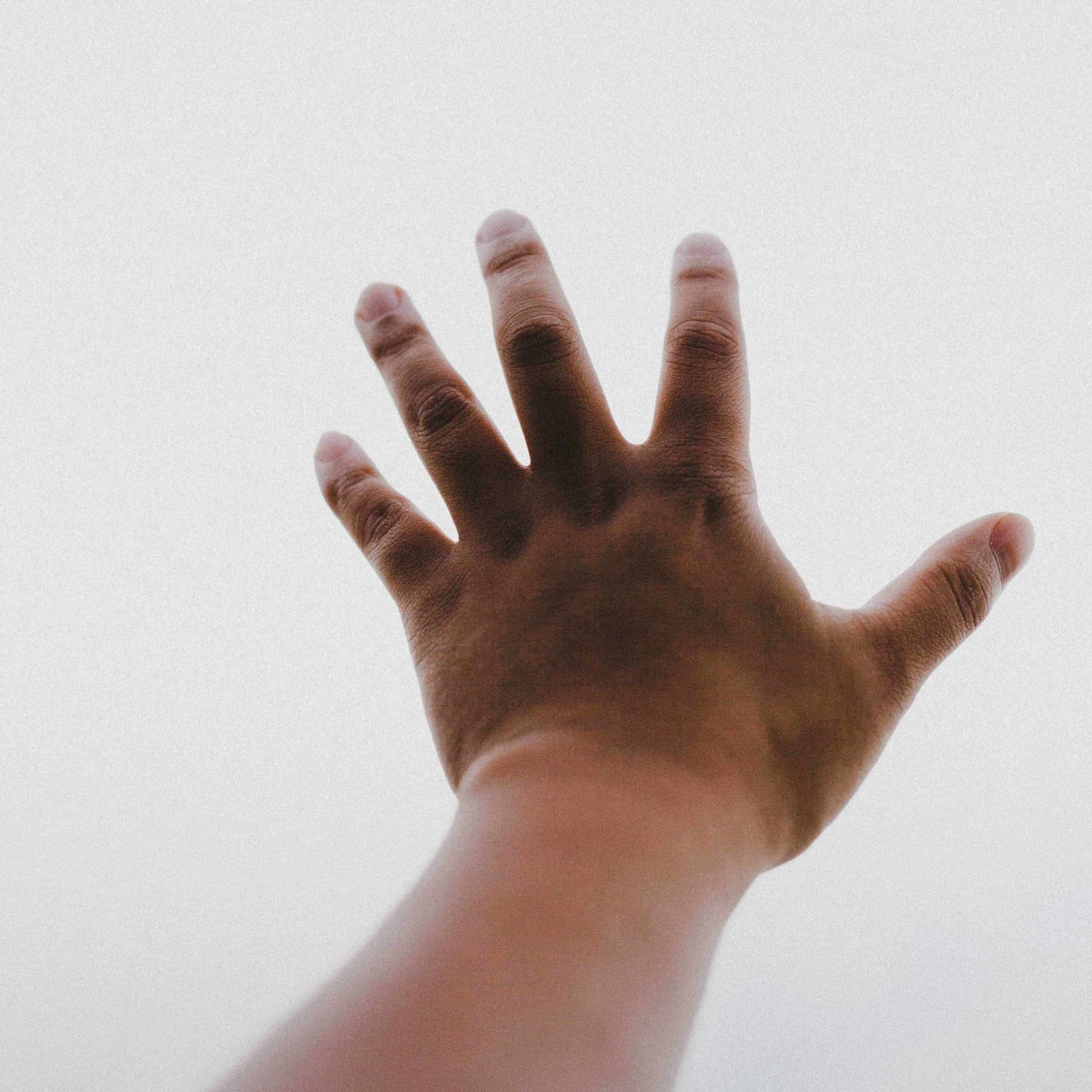 Hand reaching towards the sky