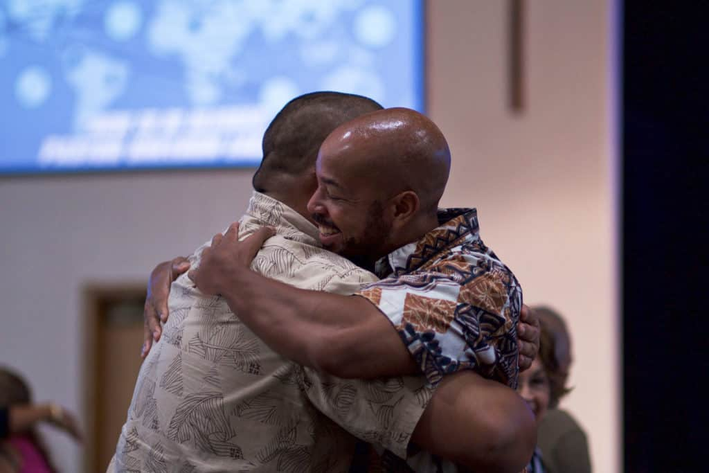 Two friends hugging at church.