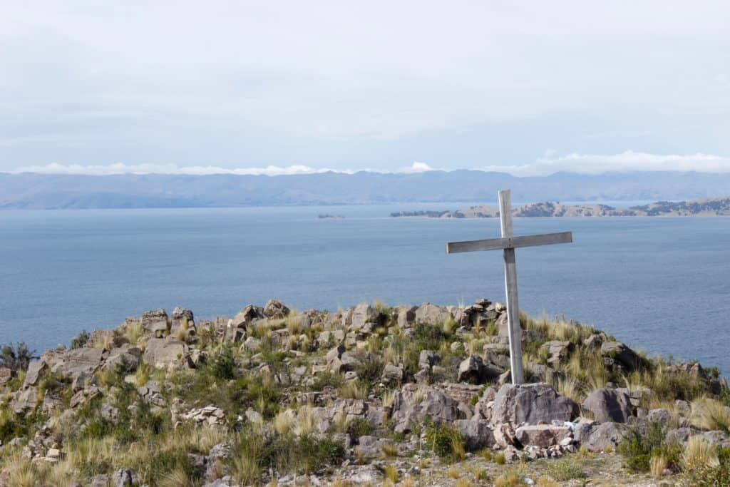 The cross on a rocky mountain with a body of water in the background.