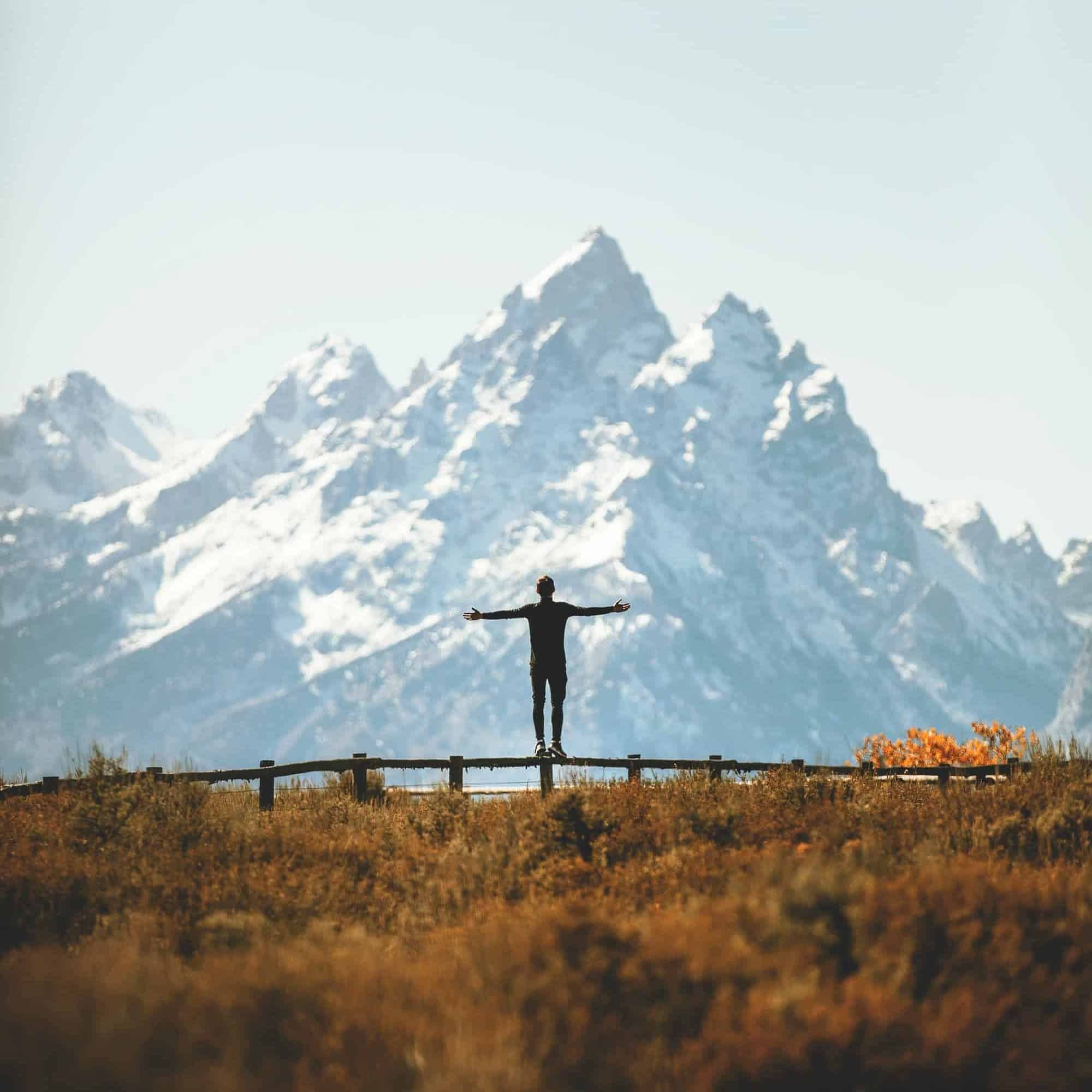 A man looking at a mountain with his arms outstretched.