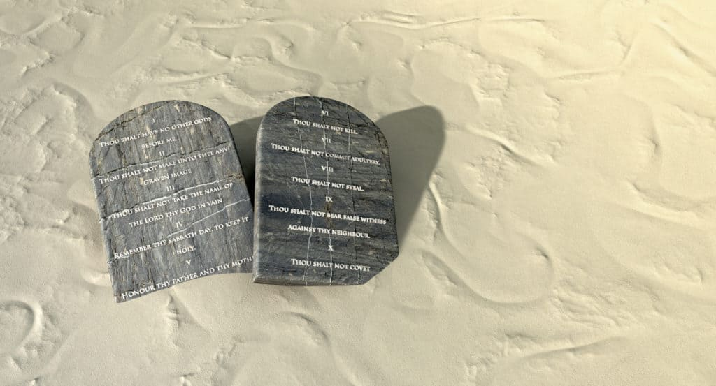 Two stone tablets with the ten commandments inscribed on them lying on tan desert sand
