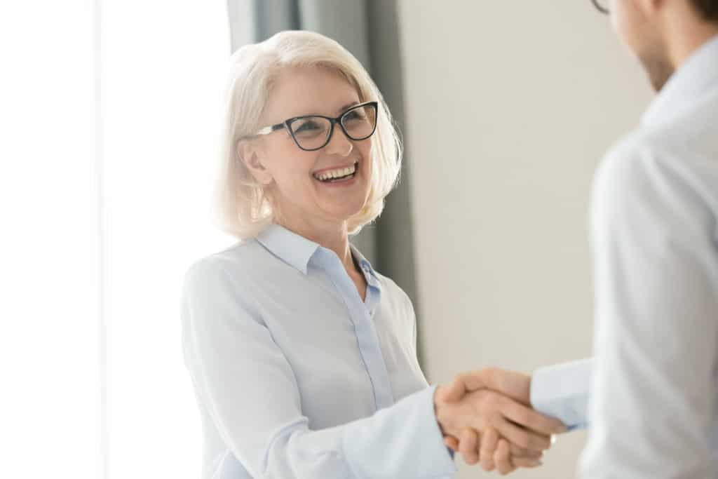 Happy older mature woman shaking hand of man