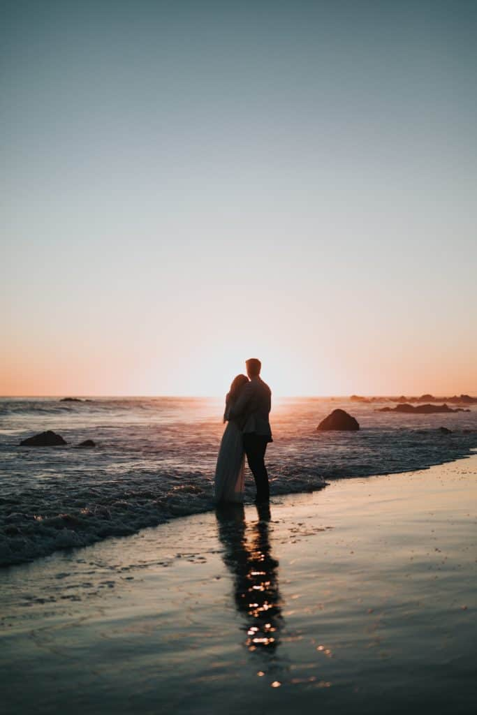 A couple standing on the beach looking at the sunset.