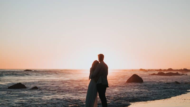A couple standing on the beach looking at the sunset as God prepares us today to enter into the Millennium