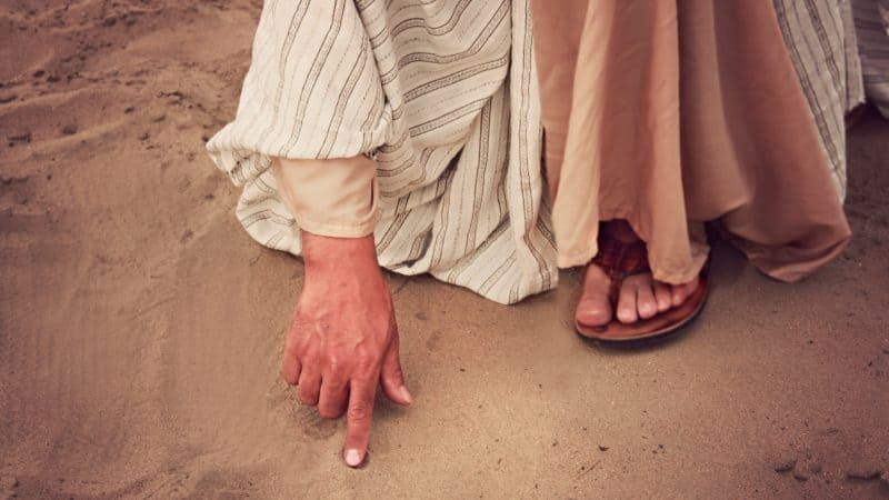 Jesus writing in the sand as the religious leaders bring a woman caught in adulatory to Him