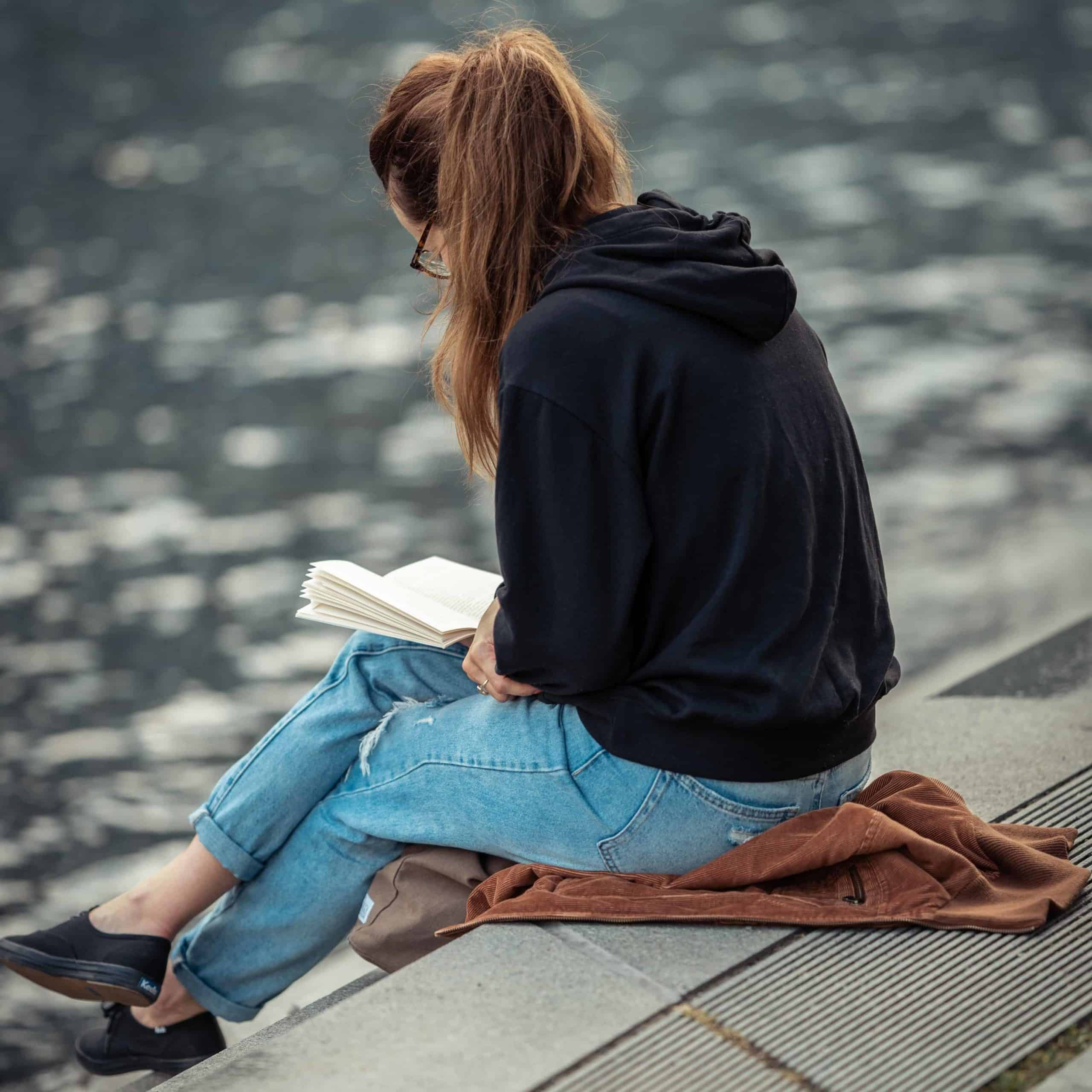 A young woman sitting on a dock reading