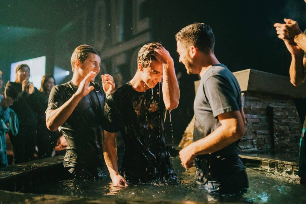 A young man getting baptized and people celebrating