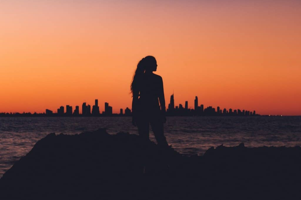 A silhouette of a woman looking at a city skyline at sunset.