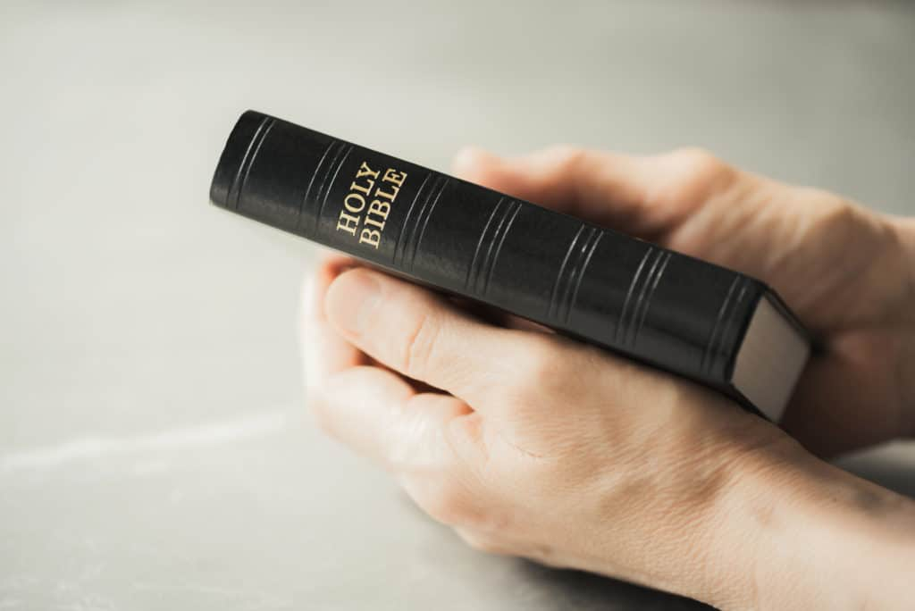 Hands holding Holy Bible over grey background.