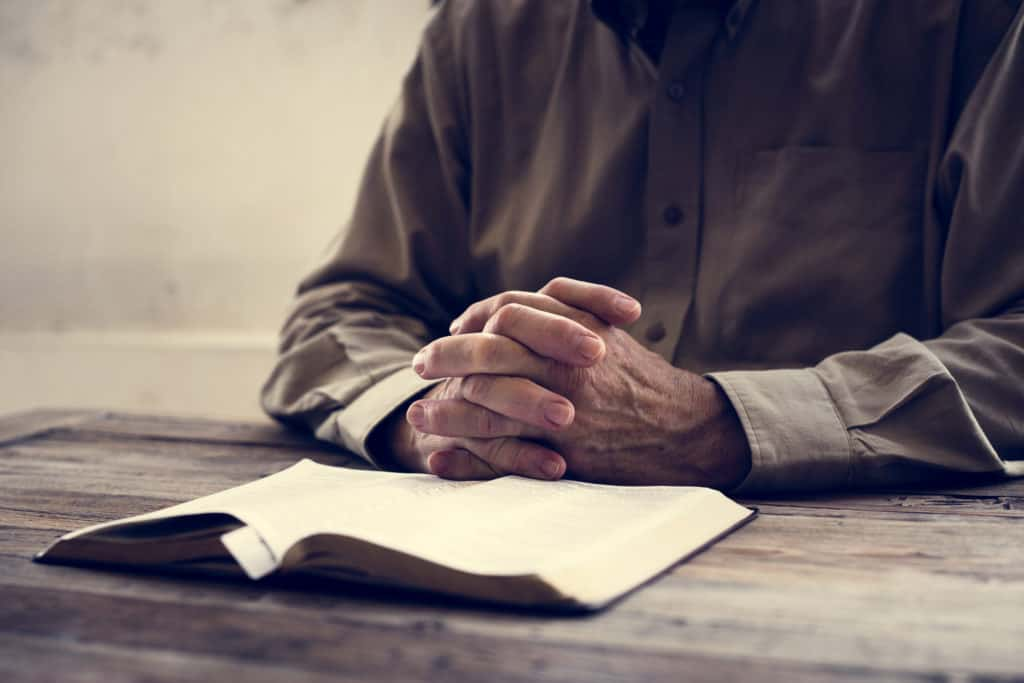 An old man reading the Bible with his hands folded in front of him.