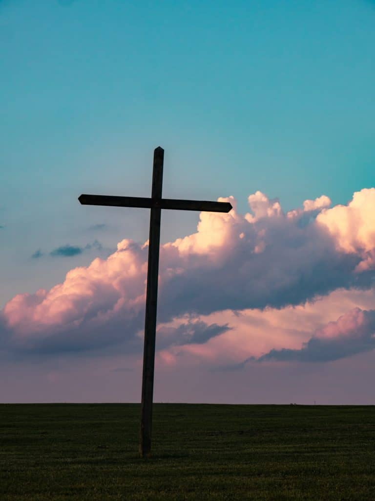 Silhouette of the cross in a field against a cloudy sunset.