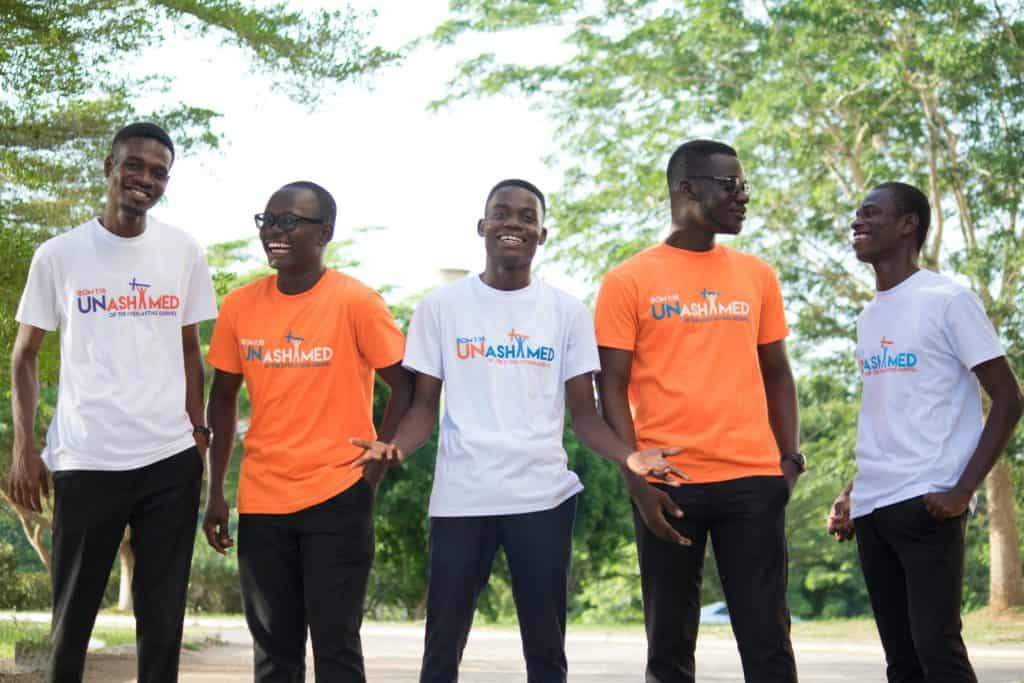 Five happy friends wearing shirts that say 'unashamed'