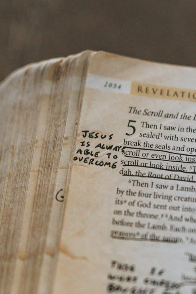 The Bible open to Revelation with 'Jesus is always able to overcome' written in the margin.