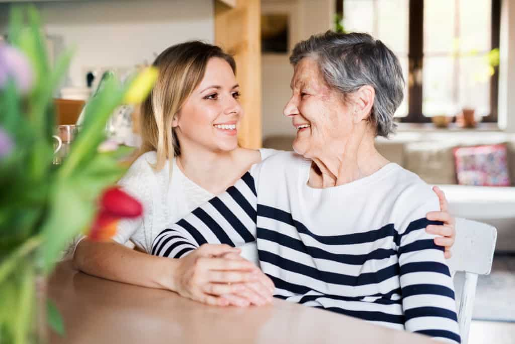 Portrait of an elderly grandmother with an adult granddaughter at home.