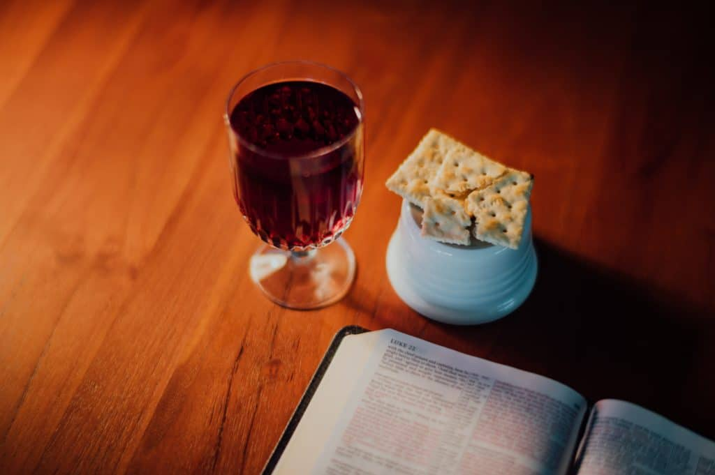 The communion wine and bread next to a Bible on a table.