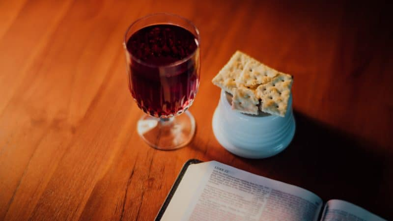 Glass of wine and broken bread next to an open Bible as Jesus gave us the ordinance of the Lord's Supper