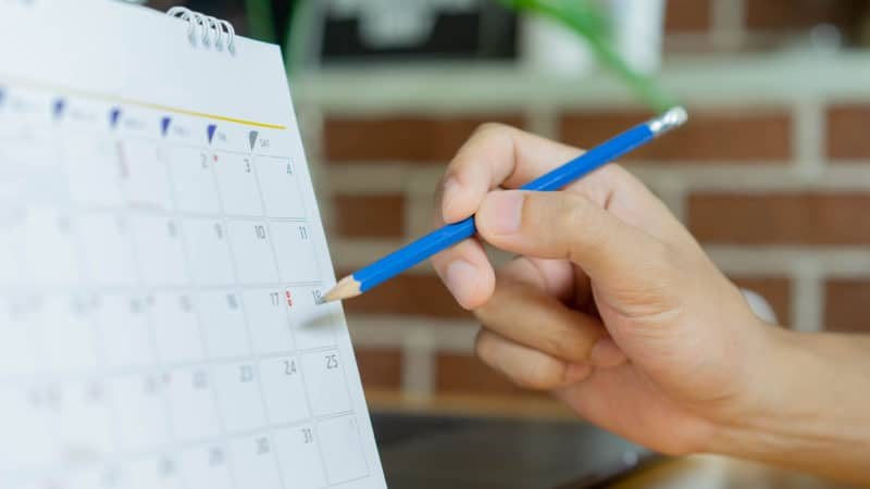 Close-up of a person marking a calendar with a pencil.