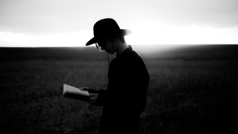 A young man standing in a field reading the Bible.