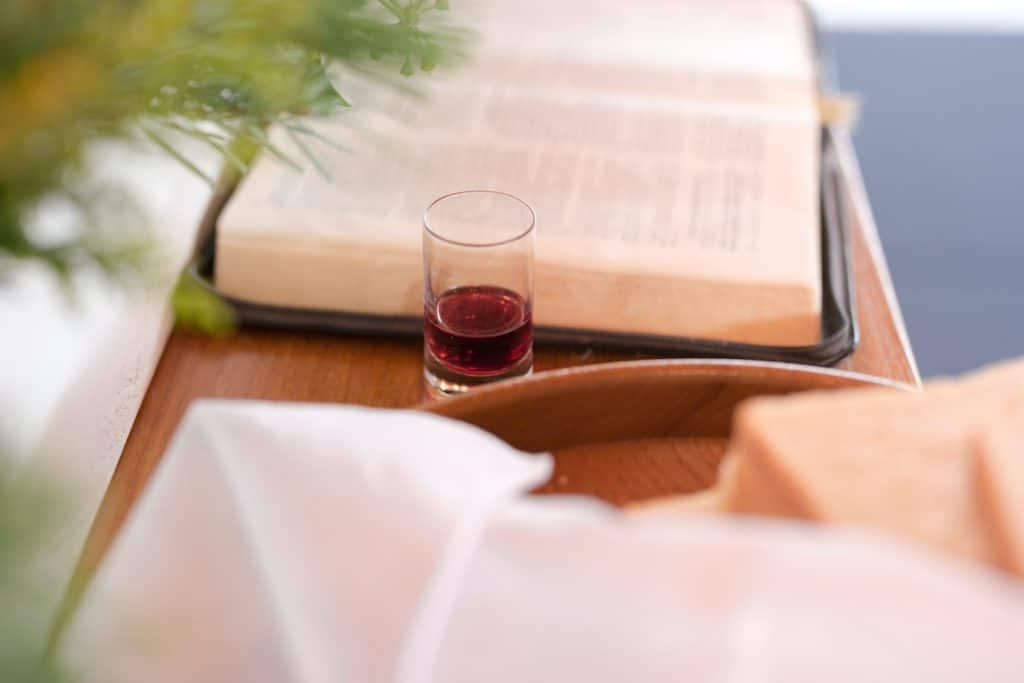 The communion wine and bread next to a Bible.