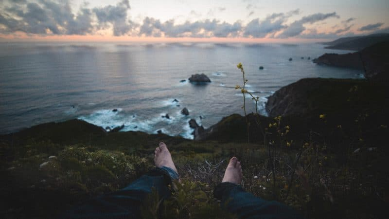 A person sitting on a grassy cliff looking out over the vast expanse of sea below and clouds above