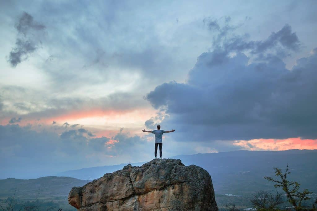 A person standing on the top of a boulder looking at the cloudy sky with their arms outstretched.