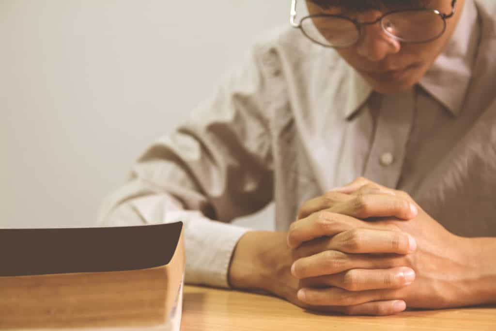 close up of a man praying with a Bible next to him on the table.
