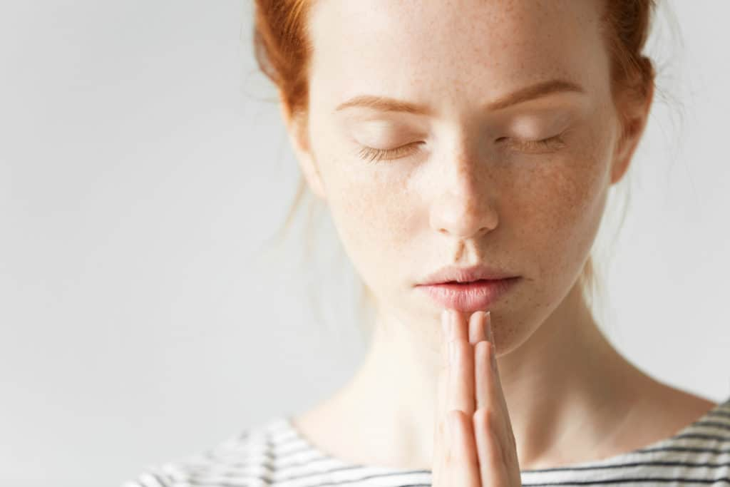 closeup of a young woman with read hair praying with her eyes closed and hands folded