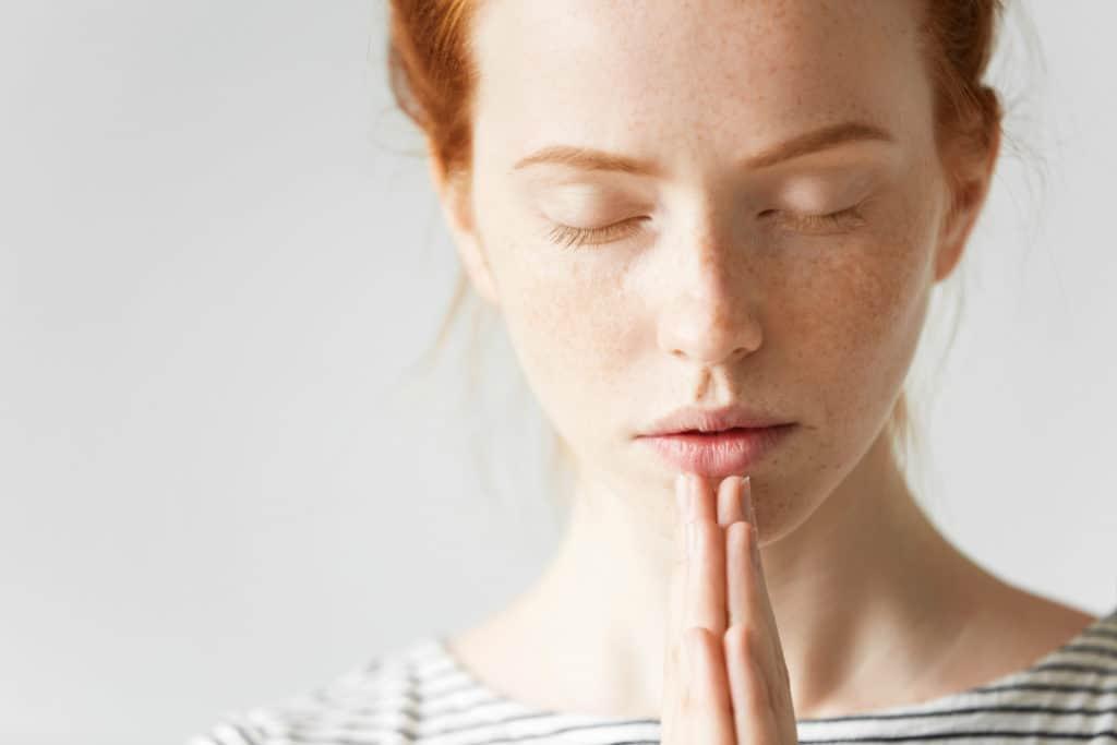 A young woman praying.