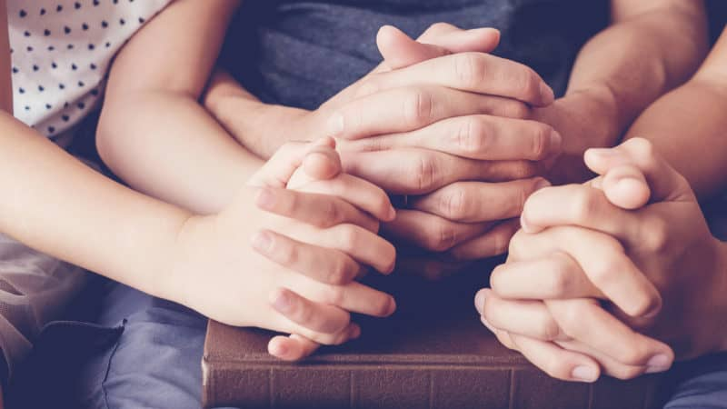 Children praying with parent at home. Closeup of hands on a Bible.