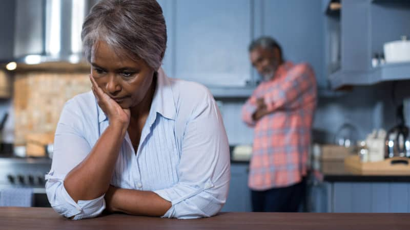 Sad woman with man in background at home as we study Biblical principles to resolve conflicts in marriage