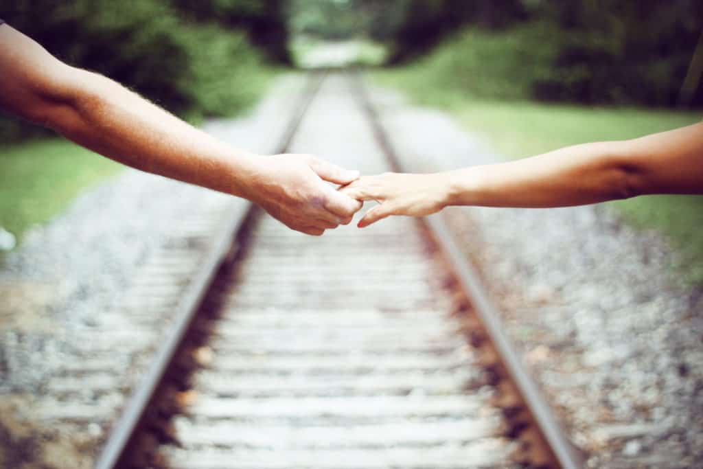 Two people reaching over a railroad to hold hands.
