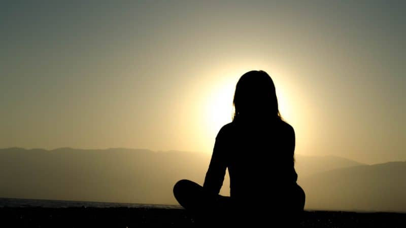 A silhouette of a woman sitting outside looking at the setting sun as we study Biblical counsel on difficult marital situations