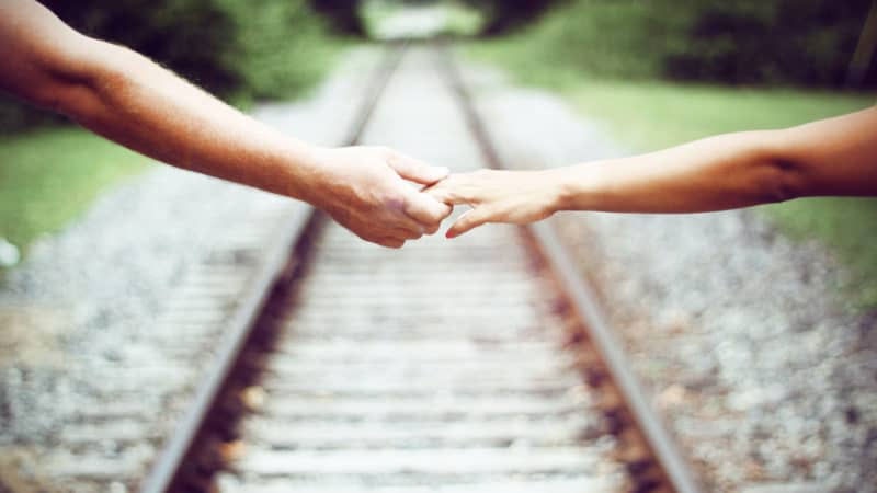 Married couple reaching over a railroad to hold hands as we study in the Bible about the love in marriage
