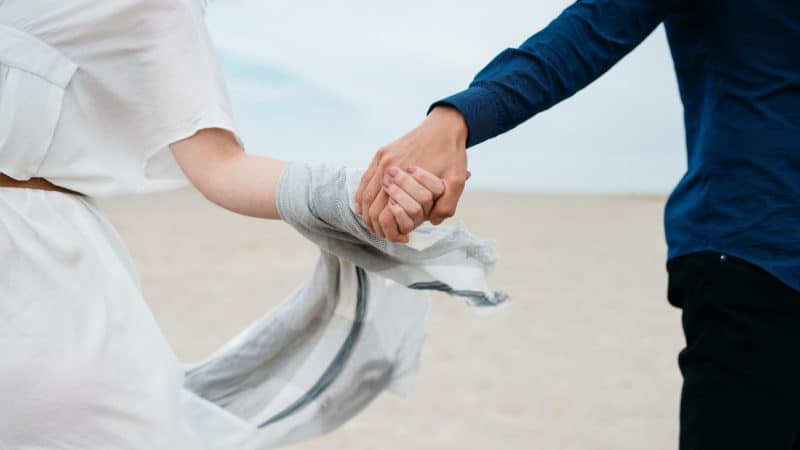 Married couple holding hands outside as we study the Biblical principles on marriage and family