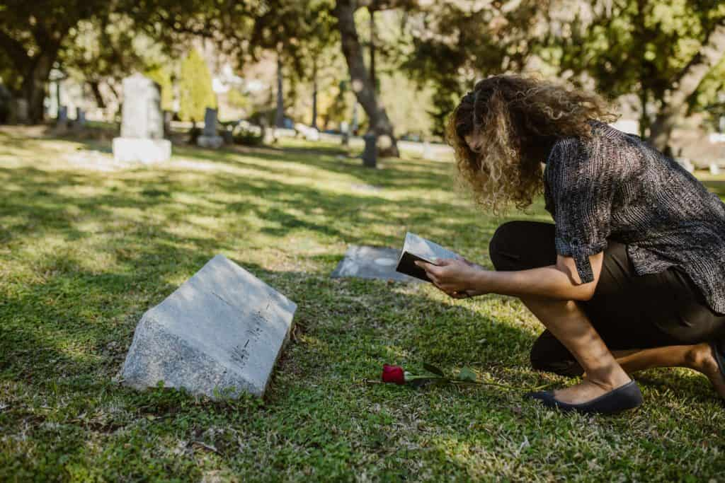 A woman reading a Bible at a grave.