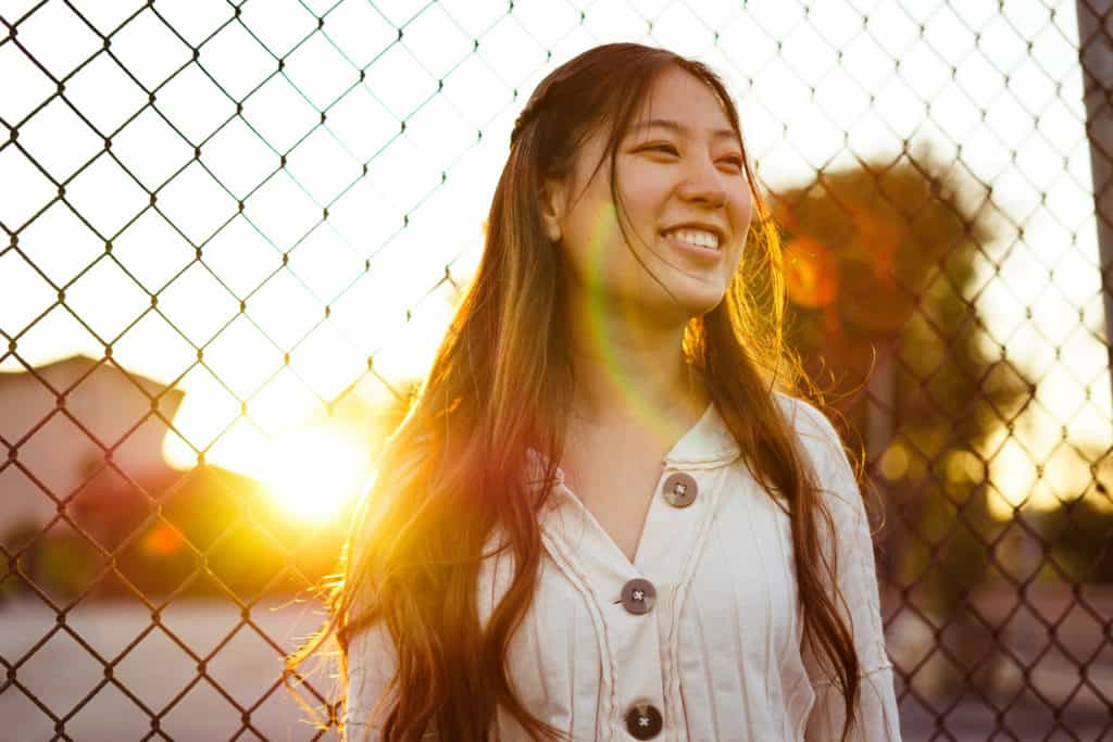 A smiling woman with the sun setting behind her.
