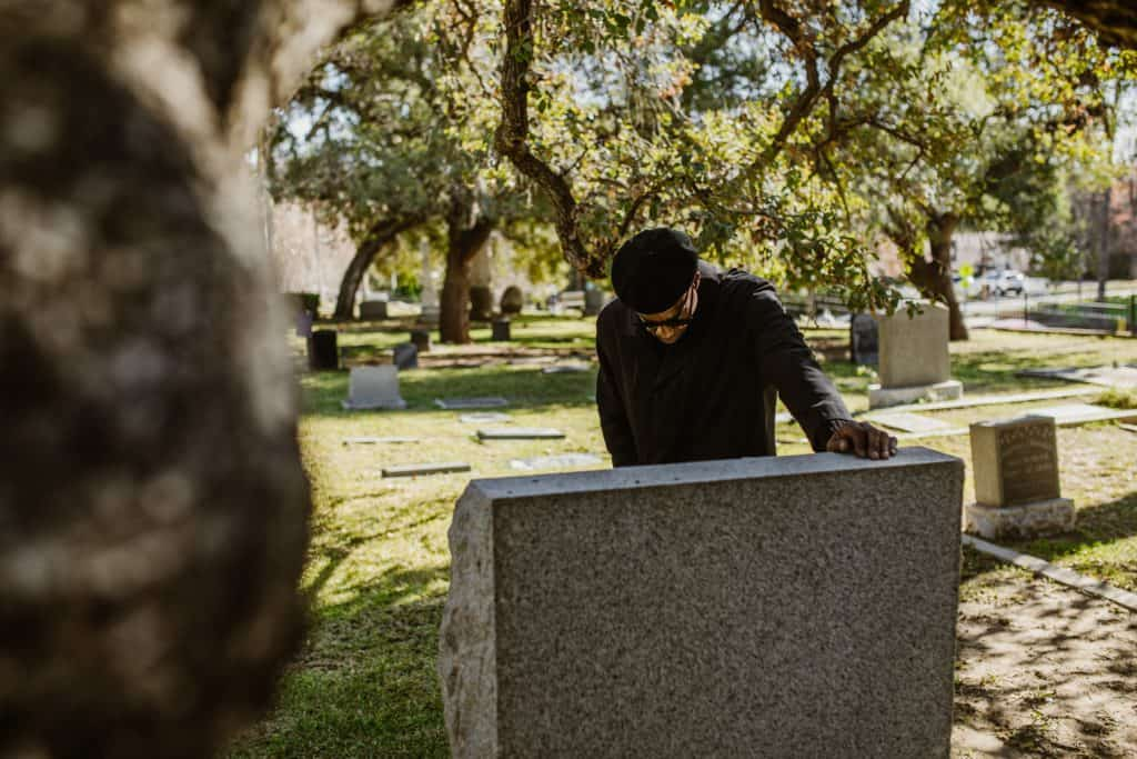 A man grieving at a grave.