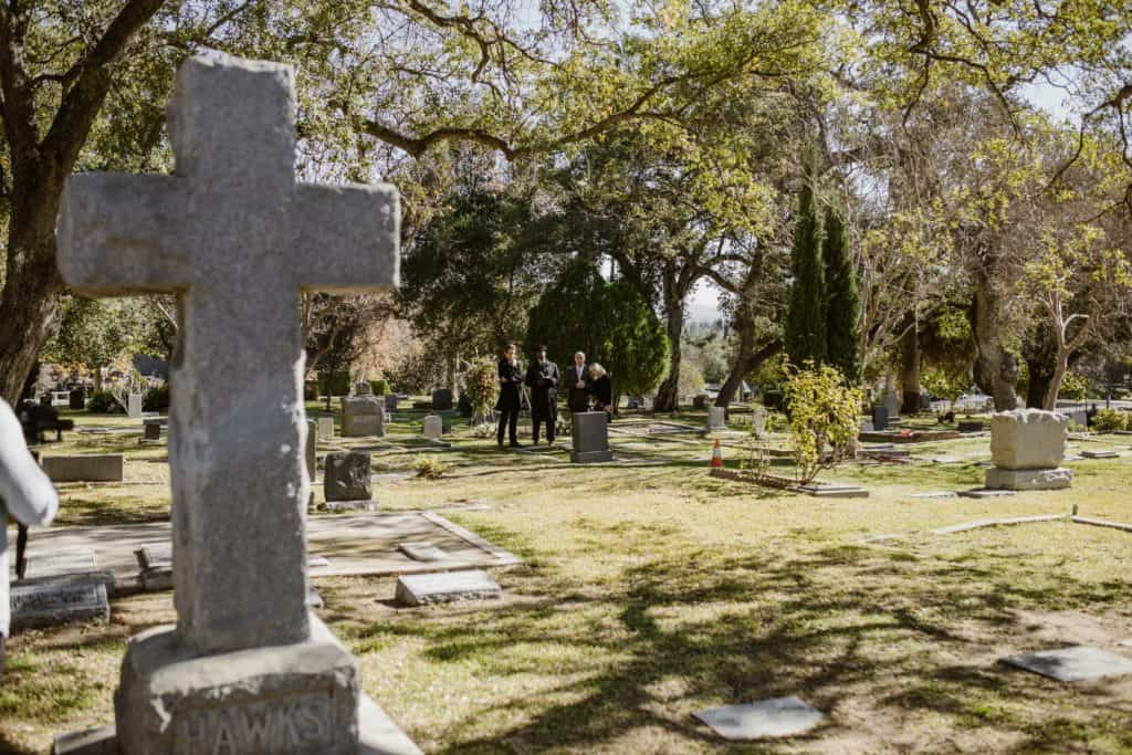 People in a graveyard standing by a grave.