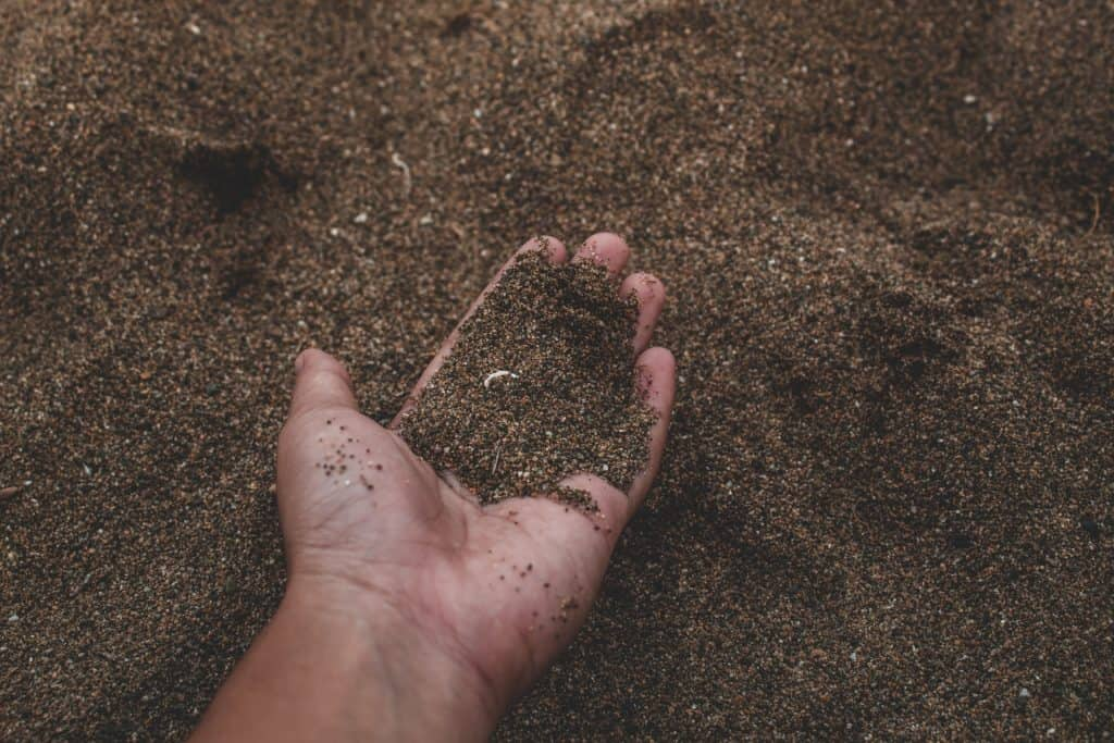 A person holding a handful of sand.
