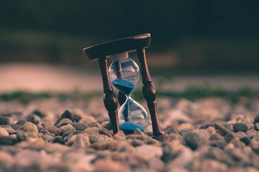 An hourglass on a rocky ground.