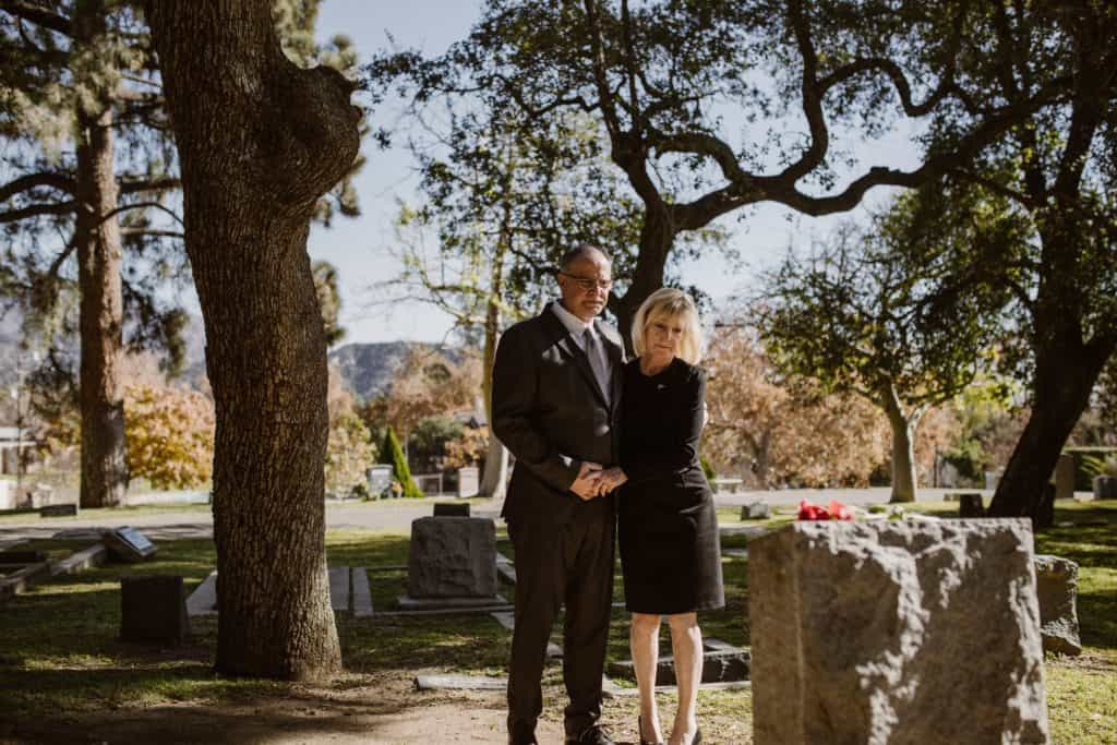 A couple holding hands at a grave.