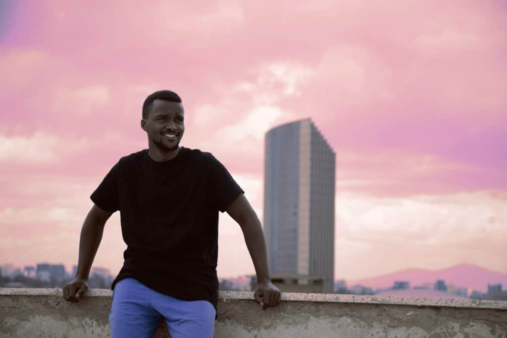 A happy man in front of a cityscape.