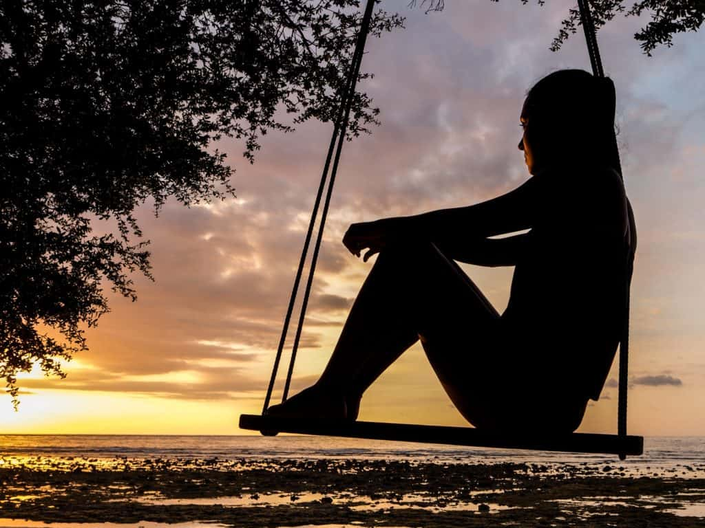 A woman sitting on a swing looking out over the water at sunset.