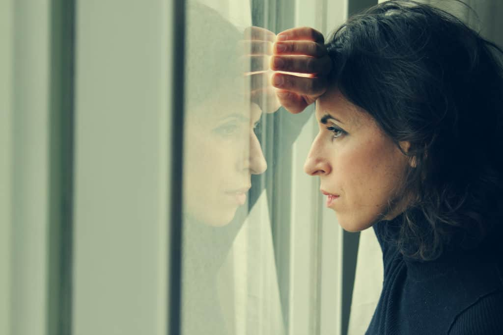 Woman stands in front of the window, looking out.