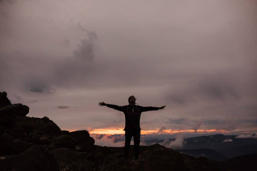A person standing on a mountain with their arms outstretched.